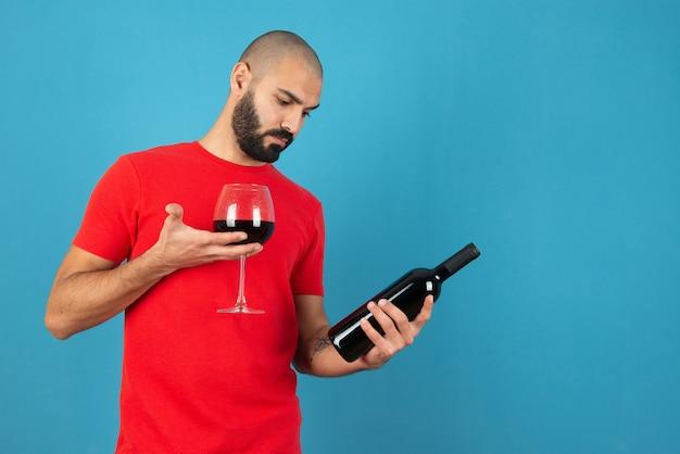 Bild eines modells des jungen mannes im roten t-short, das eine flasche wein mit glas hält.