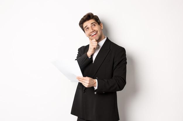 Bild eines nachdenklichen, gutaussehenden geschäftsmannes im schwarzen anzug, der das dokument hält und die obere rechte ecke betrachtet, denkt und lächelt, vor weißem hintergrund stehend
