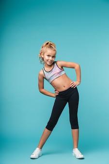 Bild eines niedlichen kleinen mädchenkindes machen fitnessübungen lokalisiert über blaue wand.