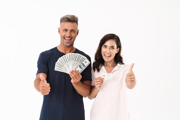 Bild eines optimistischen erwachsenen liebespaares, das über weiße wand isoliert ist und geld und kreditkarte hält, die daumen nach oben zeigen.