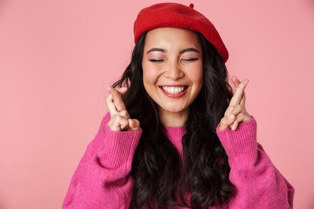 Bild eines positiven schönen asiatischen mädchens mit langen dunklen haaren, das eine baskenmütze trägt und die daumen für viel glück drückt