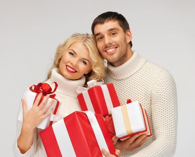 Bild eines romantischen paares in einem pullover mit geschenkboxen