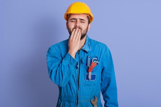 Bild eines schläfrigen, erschöpften baumeisters, der gähnt, seinen mund mit der hand bedeckt, die augen schließt, einen bart hat, uniform und helm trägt, arbeitsmüde ist und den wunsch hat zu schlafen. menschen- und arbeitskonzept.