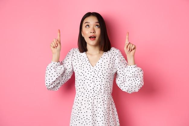 Bild eines schönen asiatischen mädchens im kleid, das mit den fingern nach oben zeigt und verträumt auf das promo-angebot starrt ...
