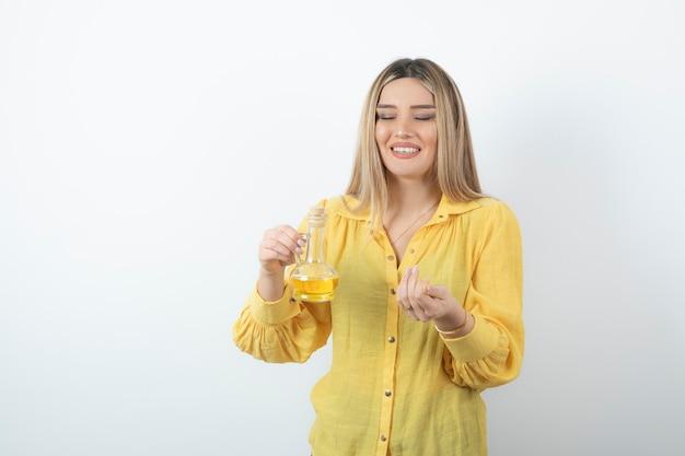 Bild eines schönen frauenmodells im gelben hemd, das eine glasflasche öl hält