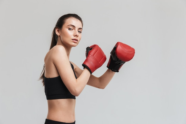 Bild eines schönen jungen sport-fitness-frauenboxers, der über grauer wand isoliert ist, macht übungen in handschuhen.