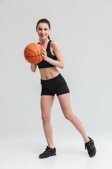 Bild eines schönen jungen sport-fitness-frauenspielers machen übungen basketball über grauer wand isoliert.
