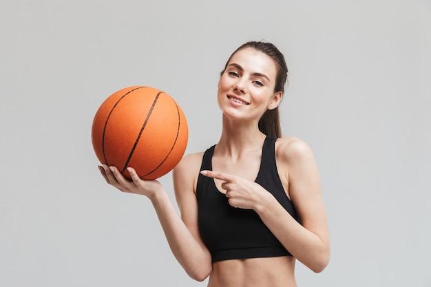 Bild eines schönen jungen sporteignungsfrauen-basketballspielers, der mit basketball lokalisiert über grauer wand aufwirft.