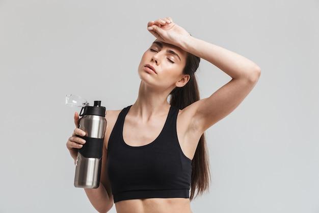 Bild eines schönen jungen trinkwassers der sporteignungfrau lokalisiert über grauer wand.