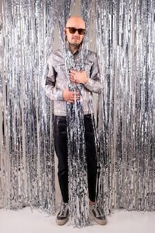 Bild eines schönen kaukasischen mannes ohne haare mit schwarzer sonnenbrille in einem glänzenden hemd, schwarzen lederhosen und grauen turnschuhen, die über silbernen glitzervorhängen aufwerfen