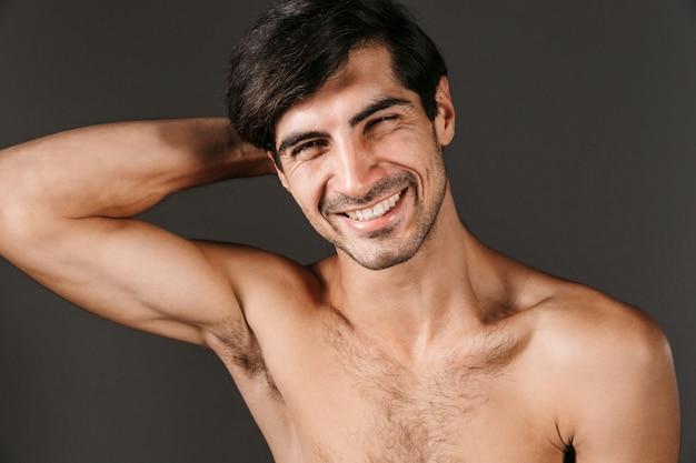 Bild eines schönen nackten jungen lächelnden mannes, der isoliert aufwirft.