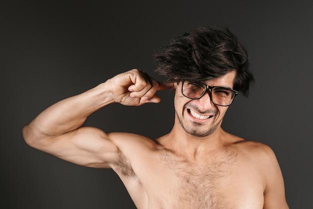Bild eines schönen nackten jungen mannes, der isoliertes tragen der brille abdeckt, die ohr bedeckt.