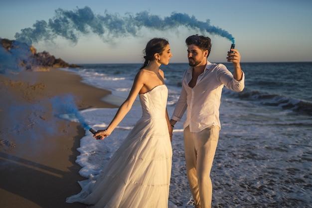 Bild eines schönen paares, das mit einer blauen rauchbombe im strand aufwirft