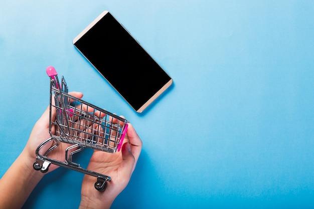 Bild eines smartphone oder des mobiltelefons und eines einkaufswagens auf einem hellblauen hintergrund - online-einkaufskonzept.