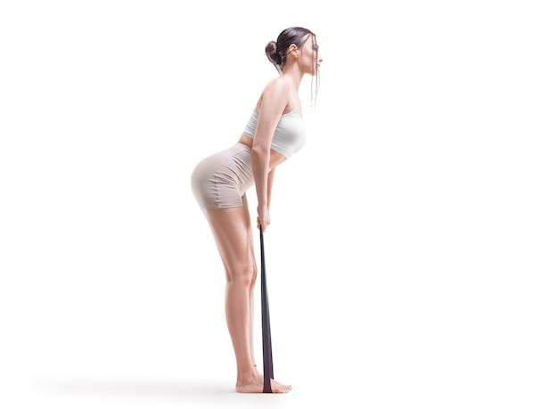 Bild eines sportlichen mädchens, das trizepsheben mit gummiband macht. das konzept von bodybuilding, pilates, stretching. gemischte medien