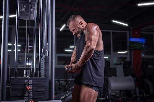 Bild eines starken athleten, der gewichte im fitnessstudio hebt. schulterpumpen. fitness- und bodybuilding-konzept. gemischte medien