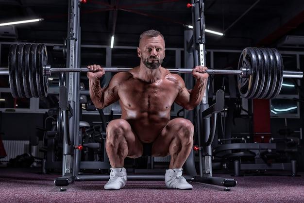 Bild eines starken sportlers, der mit einer langhantel in einem fitnessstudio hockt. fitness- und bodybuilding-konzept. gemischte medien