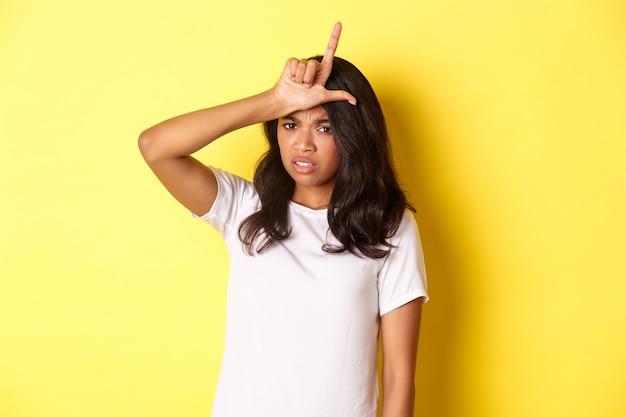 Bild eines traurigen afroamerikanischen mädchens, das ein verliererzeichen auf der stirn zeigt und sich unsicher und lahm fühlt