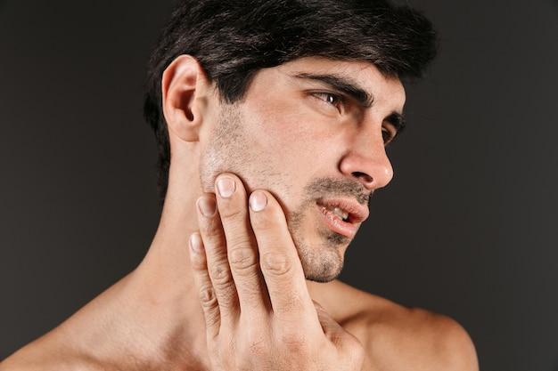 Bild eines traurigen unzufriedenen jungen mannes mit zahnschmerzen, die isoliert aufwerfen.