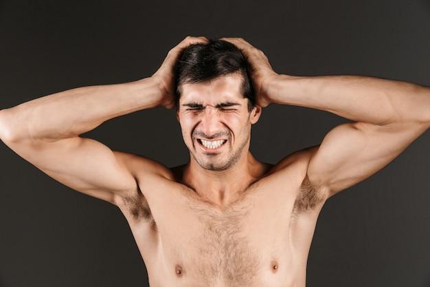 Bild eines unzufriedenen jungen mannes mit kopfschmerzen, die isoliert aufwerfen.