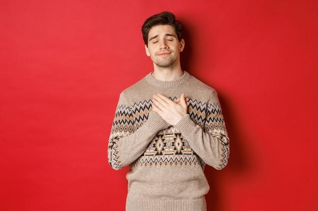 Bild eines verträumten und glücklichen, attraktiven bärtigen mannes im weihnachtspullover, der die hände auf dem herzen hält, mit geschlossenen augen lächelt, sich an etwas berührendes erinnern, neues jahr feiern, roter hintergrund.