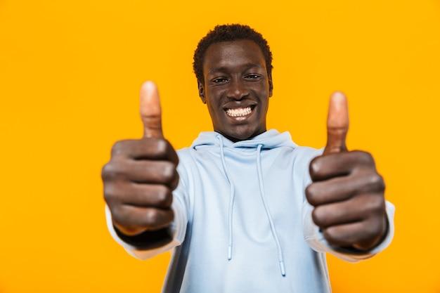 Bild eines zufriedenen afroamerikaners im streetwear-hoodie, der lächelt und daumen nach oben zeigt