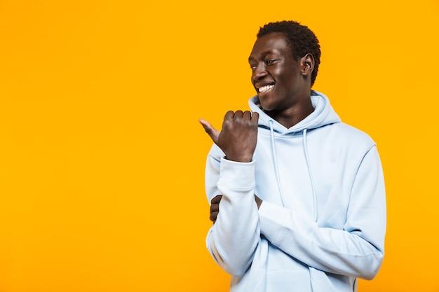 Bild eines zufriedenen afroamerikaners im streetwear-hoodie, der lächelt und mit dem finger auf das exemplar zeigt