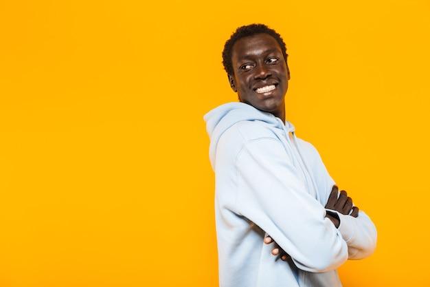 Bild eines zufriedenen afroamerikaners im streetwear-hoodie, der lächelt und rückwärts auf den copyspace schaut