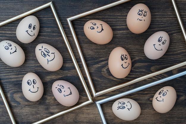Bild goldener rahmen und viele lustige eier, die auf dunklem holzwandhintergrund lächeln, nahaufnahme. eier familiengefühl gesicht porträt. konzept lustiges essen