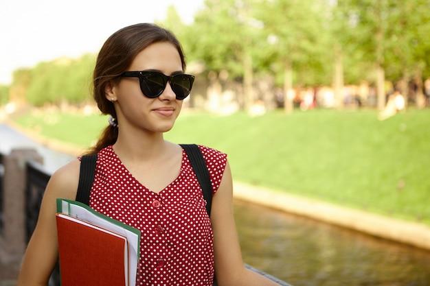 Bild im freien von fröhlicher studentin, die stilvolle schwarze sonnenbrille und rot gepunktetes kleid lächelnd trägt, fröhlichen blick hat und copybooks unter ihrem arm auf ihrem weg zur universität am morgen trägt