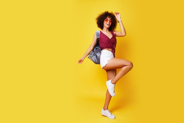 Bild in voller länge der glücklichen aktiven mischlingsfrau, die auf gelb springt