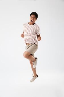 Bild in voller länge des freudigen positiven asiatischen mannes im lässigen gestreiften t-shirt, das sich mit geballten fäusten freut, isoliert