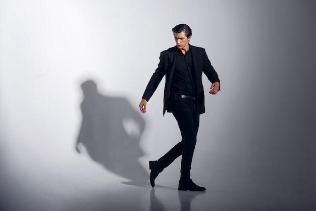 Bild in voller länge des hübschen männlichen modells im schwarzen stilvollen anzug, lokalisiert auf weißem hintergrund. horizontale ansicht.