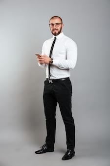 Bild in voller länge des jungen bärtigen mannes in den gläsern und in der krawatte, die auf kamera mit handy in den händen schauen, lokalisiert über graue wand