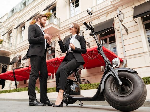 Bild in voller länge des lächelnden geschäftspaares, das nahe motorrad aufwirft