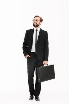Bild in voller länge des reichen geschäftsmäßigen mannes im anzug und in den brillen, die schwarze aktentasche tragen und beiseite schauen, lokalisiert über weißer wand