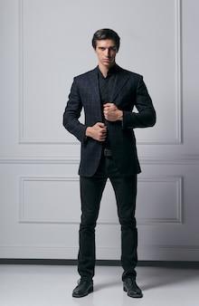 Bild in voller länge eines eleganten modemannes, der seinen anzug anpasst, während er kamera betrachtet, weg von der kamera, auf grauem hintergrund.