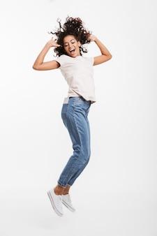 Bild in voller länge von attraktiver afroamerikanerfrau mit braunem lockigem haar, das jeans und t-shirt trägt, die mit angenehmem lächeln aufwirft, lokalisiert über weißer wand