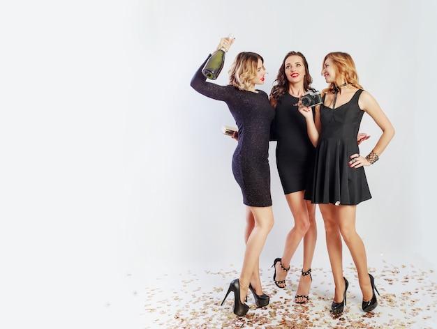 Bild in voller länge von drei glücklichen mädchen, die zeit auf verrückter party verbringen, tanzen, spaß haben und lachen. tragen sie ein elegantes freizeitkleid, absätze und ein helles make-up. champagner trinken. platz für text.
