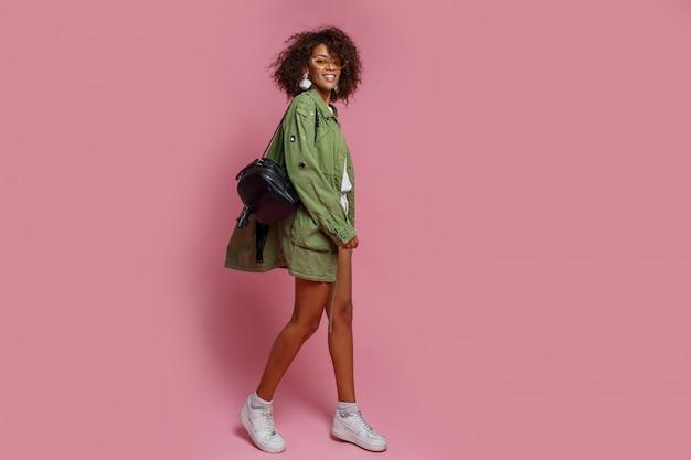 Bild in voller länge von formschöner frau mit dunkler haut in stilvoller grüner jacke auf rosa hintergrund. einkaufs- und modekonzept.