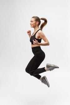 Bild in voller länge von glücklicher schöner fitnessfrau