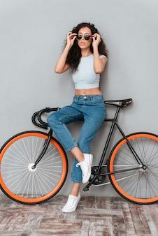 Bild in voller länge von hübscher lockiger frau in der sonnenbrille, die mit fahrrad über grauem hintergrund aufwirft