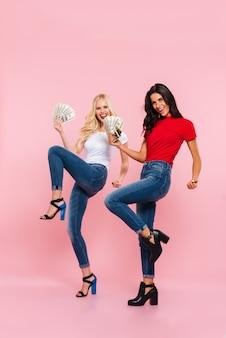 Bild in voller länge von zwei glücklichen frauen freuen sich mit geld in den händen und betrachten die kamera über rosa