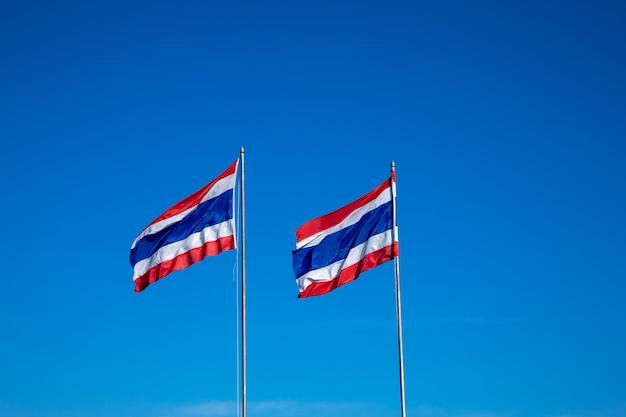 Bild von 2 thailändische flagge von thailand mit hintergrund des blauen himmels wellenartig bewegen.