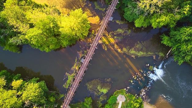 Bild von antenne mit blick auf fluss und wald mit künstlichen wasserfällen vom damm und der bahngleisbrücke