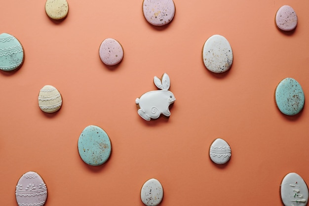 Bild von dekorierten hausgemachten lebkuchen in form von kaninchen und eiern einzeln auf orangefarbenem hintergrund