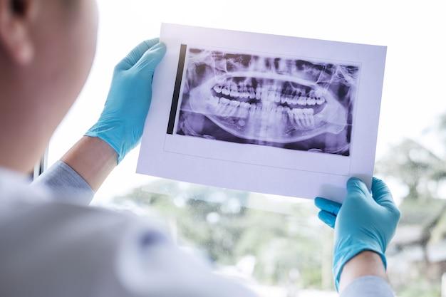 Bild von doktor oder von zahnarzt, die zahnmedizinischen röntgenstrahl halten und betrachten