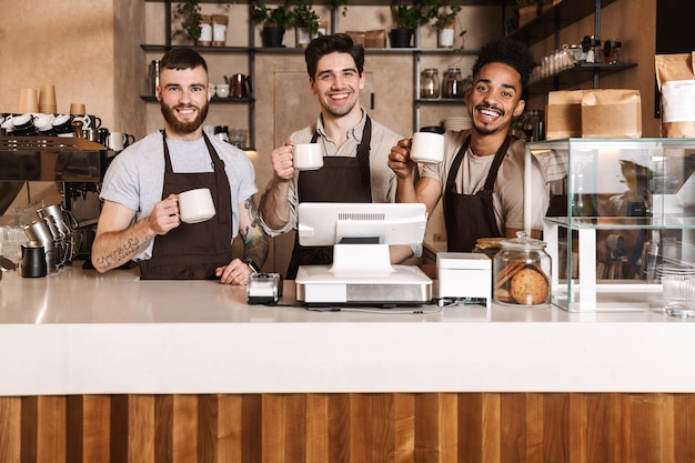 Bild von drei glücklichen kaffeemännerkollegen in der cafébar, die drinnen arbeitet.