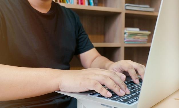 Bild von einem jungen mann arbeitet an seinem laptop in bibliothek, rückansicht der geschäftsmann hände beschäftigt mit laptop am schreibtisch, junge männliche schüler eingabe auf computer sitzen am holztisch