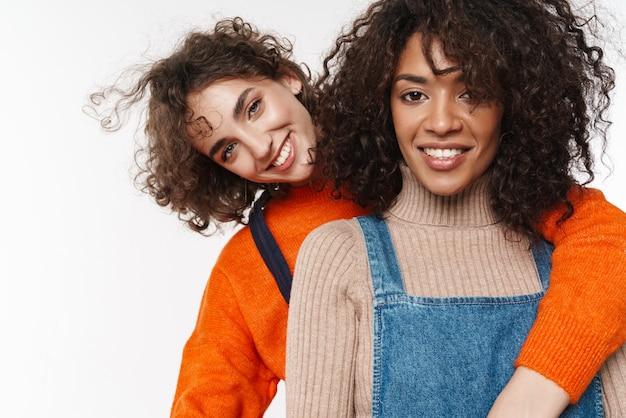 Bild von einem ziemlich glücklich lächelnden zwei gemischtrassigen freundinnen in denim-overalls